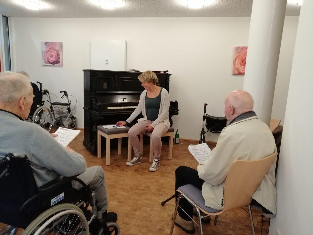 Frau Miebach begleitet das Singen am Klavier